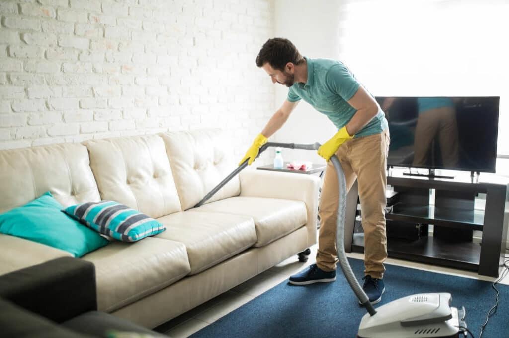 Man vacuuming/cleaning sofa